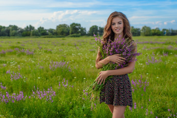 Girl in a field with lavender flowers in her hands.