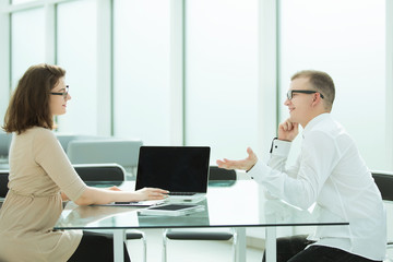 two employees are discussing something sitting at the office table
