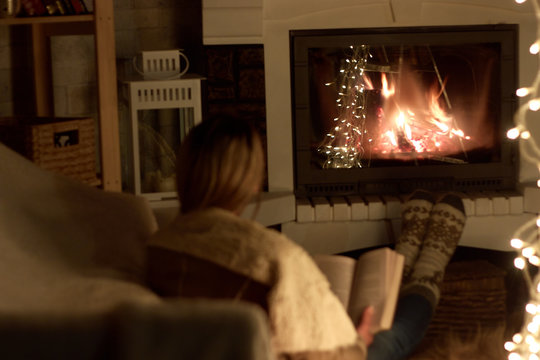 single woman reading a book in front of a fireplace on a long winter night