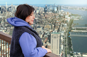 Woman suffers from a fear of heights. She is scared on the viewing platform above a big city.