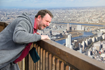 Mature man suffers from acrophobia. He is scared on the viewing platform above a megalopolis.