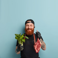 Delighted friendly looking man with thick beard, holds bok choy and fresh meat, works as chef in restaurant, prepares delicious dish from different ingredients, models over blue wall with free space