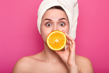 Portrait of beautiful surprised girl with towel on head and nacked shoulders. Attractive woman with wide opened eyes, covers her mouth with half of orange. Female has skin care procedure in spa salon.