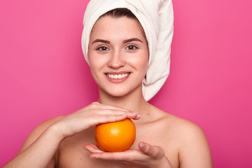 Portrait of attractive cheerful woman with white towel on head, holds orange over pink background. Young smiling female visits spa salon and has rest, takes care of her skin. Natural beauty concept.
