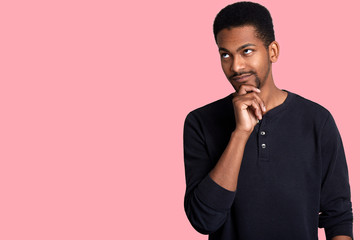 Printed kitchen splashbacks Artist KB Closeup portrait of attractive thoughtful African guy. Young handsome man looks aside, keeps hand on chin and thinks about his dream, isolated on rose background. Copy space for your advertisment.