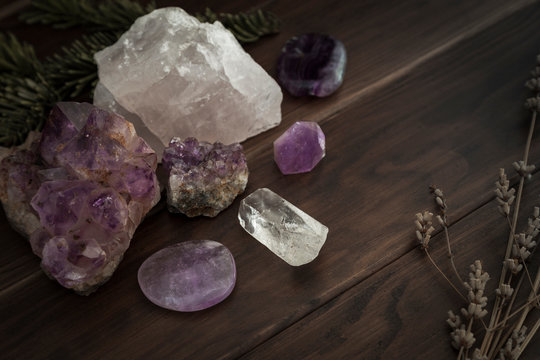 Selection of Crystals and Stones on a Wooden Surface with Foliage