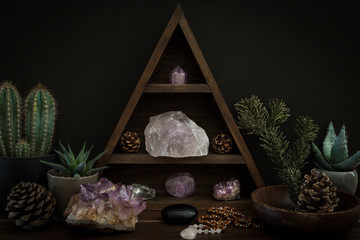 Triangular Crystal Shelf with Plants Foliage Gems and Jewellery on a Wooden Surface