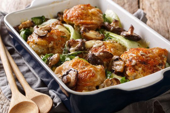 Healthy food baked chicken thighs with baby bok choy, shiitake mushrooms and cheese sauce in a rustic style closeup on the table. horizontal