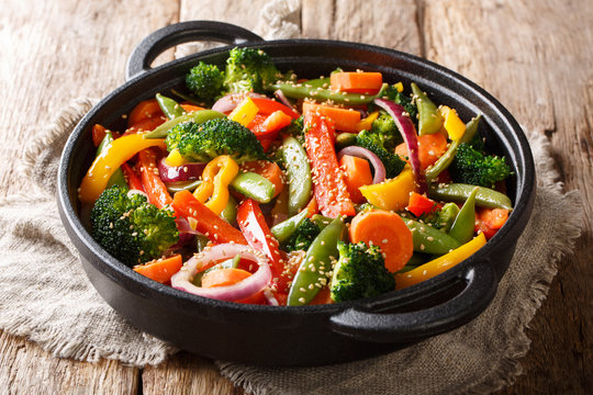 Asian cuisine fried vegetables with sesame close-up in a frying pan on the table, horizontal