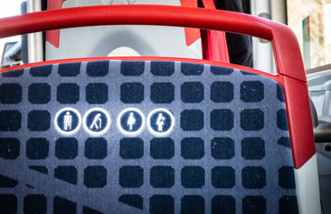 Brcelona public transport, close up of round icon priority seat for elderly, pregnant or disabled people on a bus seat