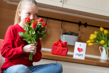 Cute young girl holding bouquet of red roses for her mom. Family celebration concept. Happy Mother's Day or Birthday Background.