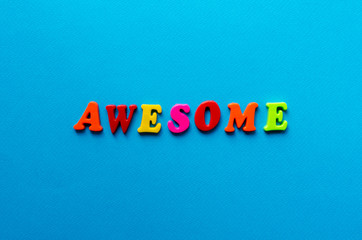 word awesome from plastic magnetic letters on blue background