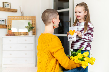 Happy Mother's Day or Birthday Background. Adorable young girl surprising her mom with homemade greeting card. Family celebration concept.