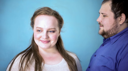 Obese couple feeling happy together, tender relationships, blue background