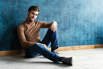 young casual fashion man sitting on the floor isolated on dark blue background. Wall mural
