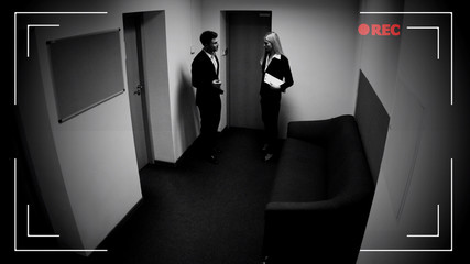 Male and female colleagues talking office corridor, CCTV camera effect, footage
