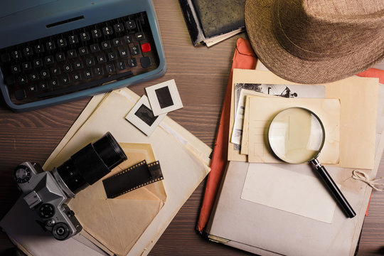 Investigator desk with confidential documents, camera, magnifying glass, vintage typewriter and hat. Secret documents investigation concept.