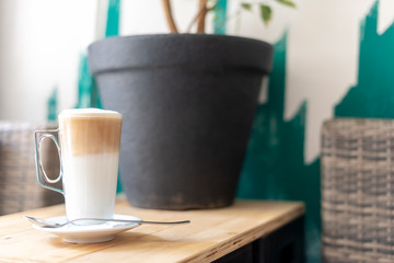 Delicious café latte in tall glass on a table in cafeteria or bistro. Milk coffee lifestyle background with copy space. Coffee break concept.