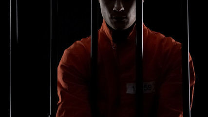 Prisoner in orange uniform standing behind bars, punishment for committed crime