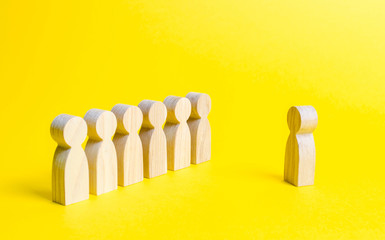 Wooden figures of people stand in the formation and listen to their leader. training, briefing and inspirational speech. Summing up, business successes and achievements. Selective focus