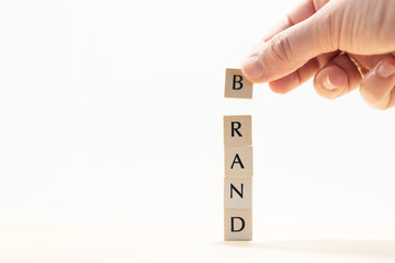 """The hand of a man forms the word """"BRAND"""" with wooden letters. Symbol image for brand building for a successful concept."""