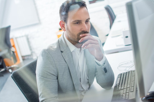 Pensive or confused business man working on computer in bright office