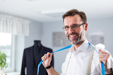 Happy tailor shop owner with measuring tape looking at camera