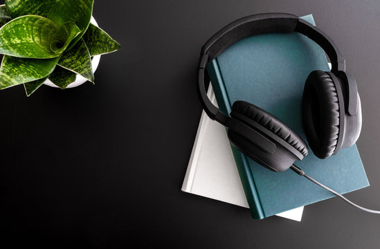 audiobook concept with overhead shot of headphones on stack of books on black background