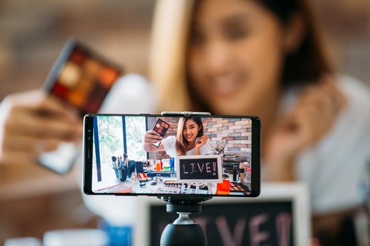 Happy young attractive Asian ethnic model filming vlog on mobile phone on tripod and showing eyeshadows at table with cosmetics
