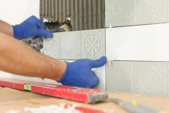 Closeup of tiler hand laying ceramic tile on wall in kitchen, renovation, repair, construction