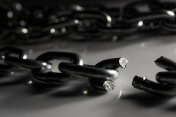 Broken chain on white surface, selective focus shallow depth of field
