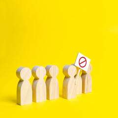 The person's figure comes out of the line with a sign on an yellow background. Social discontent and social tension, protest and disagreement. An angry mob of wooden figures of people with a poster.