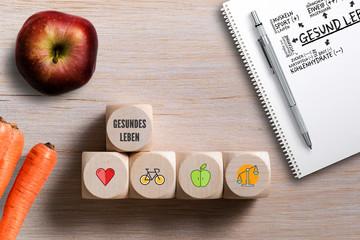 """Würfel mit Symbolen und Schiefertafel mit der Aufschrift """"gesundes Leben"""""""