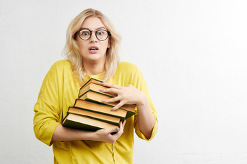 Frightened girl nerd blonde in round glasses with a worried face holding a stack of books on a white background in yellow clothes. Education and science concept