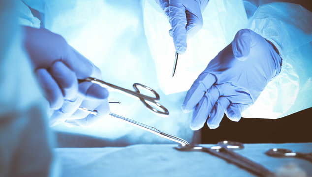 Surgeons hands holding surgical scissors and passing surgical equipment, close-up. Health care and veterinary concept