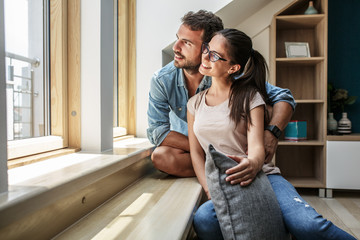Portrait of young couple.They sitting by the window in living room.