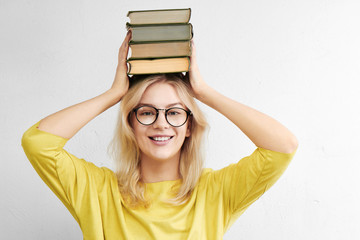 A beautiful woman in glasses is holding a stack of books above her head and is smiling toothyly on a white background. Happy and fun education