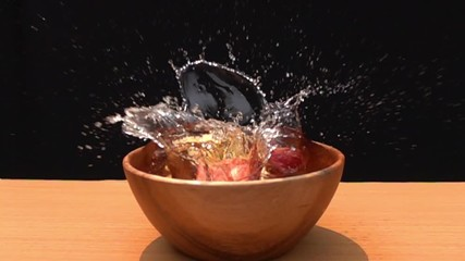 Fototapete - Slices of red apple falling to the water in a wooden bowl in Slow Motion