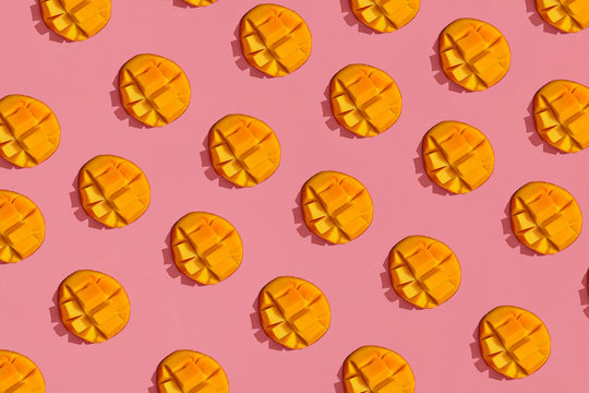 Colorful fruit pattern of fresh juicy cutted mango on coral pink background, top view