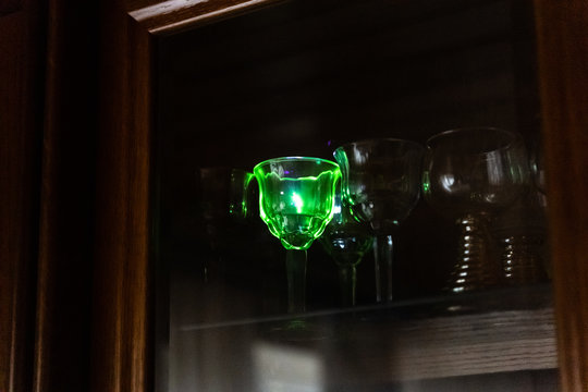 Strong blue laser pointer hits a crystal glass