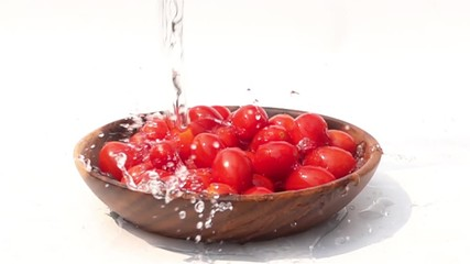 Fototapete - Pouring fresh water on a pile of Cherry Tomato in a wooden Bowl on white background in Slow Motion