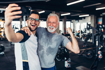 .Senior man taking selfie photo with his personal trainer while exercising at gym.