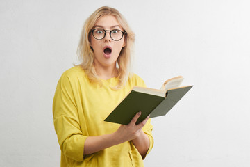 Young blonde in round glasses reads a book with a surprised face in yellow clothes. Isolated in white studio.