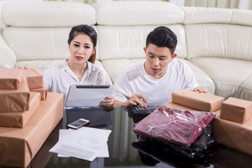 Asian couple counting their online selling report