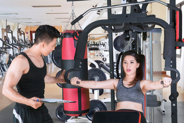 Asian woman uses machine exercise with her trainer