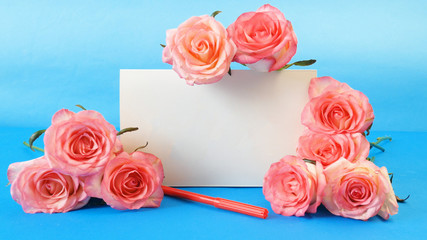pink roses and white blank and pencil on blue background