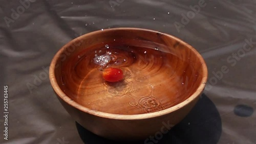 Fototapete Cherry tomatoes falling to the water in wooden bowl in Slow Motion