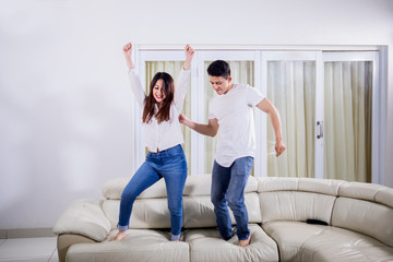 Cheerful couple dancing together on the couch