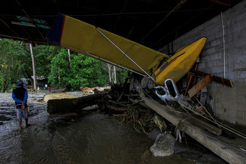 Man walks near an aircraft damaged following a flash floods in Sentani, Papua