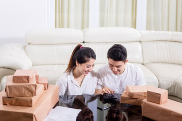 Happy couple counting their online selling report